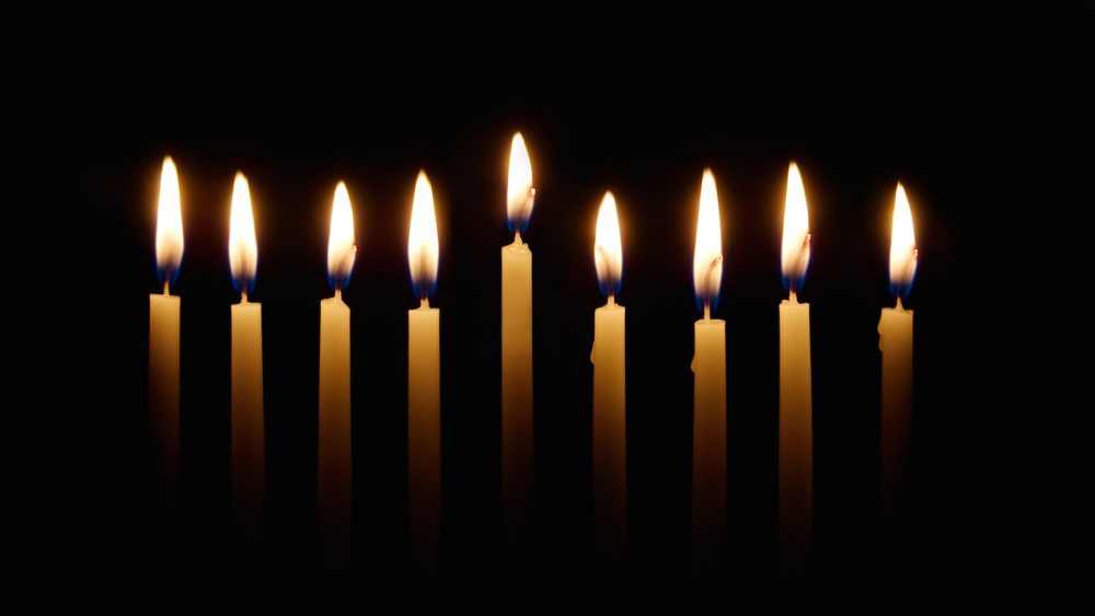 Glowing candles lit for the eighth night of Hanukkah