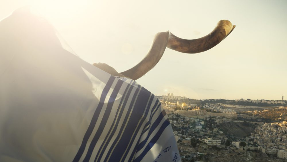 Jewish man blowing the Shofar with view of the holy city of Jerusalem